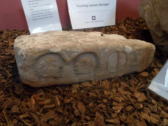 Stone on display at Wall museum, featuring two carved heads and what's thought to be a shield.